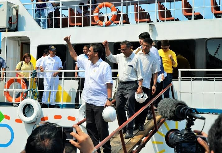 """Sec. Mar Roxas and Rep. Jess Manalo flash thumbs up signs after the maritime party representative gave the cabinet secretary a tour of """"Island Evisa,"""" the first steel hull trimaran designed and built by Filipinos."""